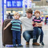 Father and two little sibling boys at the airport Stock Images