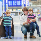 Father and two little sibling boys at the airport Royalty Free Stock Photos