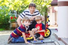 Father and two little sibling boys reparing broken bicycle Royalty Free Stock Images