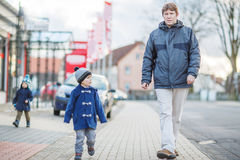 Father and two little sibling boys walking on the street in Germ Stock Photo