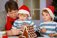 Father and two little sons preparing a gingerbread cookie house Royalty Free Stock Photography