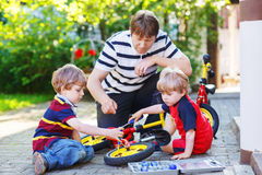 Father and two little sons reparing bikes together Stock Photography