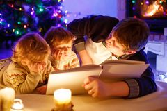 Father and two little toddler boys reading book by chimney, candles and fireplace. Family celebrating Christmas. With Xmas tree and lights on background. Kids royalty free stock images