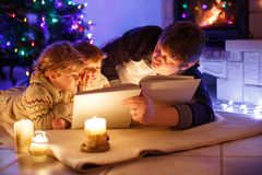 Father and two little toddler boys reading book by chimney, candles and fireplace. Family celebrating Christmas. With. Xmas tree and lights on background. Kids royalty free stock images