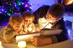 Father and two little toddler boys reading book by chimney, candles and fireplace. Family celebrating Christmas. With Xmas tree and lights on background. Kids Royalty Free Stock Photography