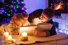 Father and two little toddler boys reading book by chimney, candles and fireplace. Family celebrating Christmas. With Xmas tree and lights on background. Kids stock photo