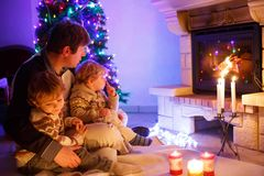Father and two little toddler boys sitting by chimney, candles and fireplace and looking on fire. Family celebrating royalty free stock images