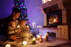 Father and two little toddler boys sitting by chimney, candles and fireplace and looking on fire. Family celebrating. Christmas. With Xmas tree and lights on royalty free stock image