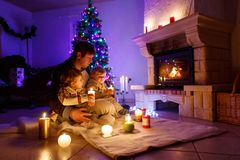 Father and two little toddler boys sitting by chimney, candles and fireplace and looking on fire. Family celebrating Christmas. With Xmas tree and lights on royalty free stock photography