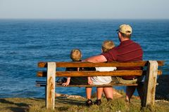 Father and two sons. Father and his two sons on a bench looking out over the ocean Royalty Free Stock Photography