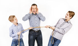 Father and two sons connected by rope. Caucasian siblings boys tied father rope and pull him isolated on white background. Concept of emotions Stock Images