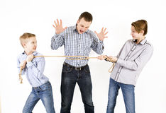 Father and two sons connected by rope. Caucasian siblings boys tied father rope and pull him isolated on white background. Concept of emotions Stock Photography