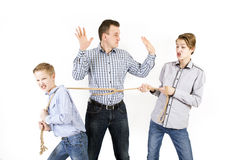 Father and two sons connected by rope. Caucasian siblings boys tied father rope and pull him isolated on white background. Concept of emotions Stock Photos