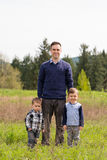 Father and Two Sons Lifestyle Portrait. Realistic lifestyle portrait of a father and his two sons outdoors enjoying nature in a field in Oregon Royalty Free Stock Photo