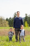 Father and Two Sons Lifestyle Portrait. Realistic lifestyle portrait of a father and his two sons outdoors enjoying nature in a field in Oregon Royalty Free Stock Photography