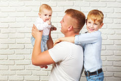 Father and two sons. Loving father and two sons on the background of brick wall Royalty Free Stock Photo