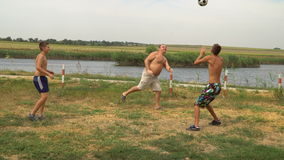 Father and two sons playing with a ball on the lake. Beach volleyball stock footage