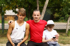 Father and two sons. Sitting on a bench Royalty Free Stock Photos