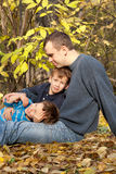 Father and two sons sitting on fallen leaves. In the park, autumn Stock Image
