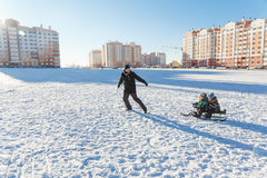 Father and two sons sledding Royalty Free Stock Photos