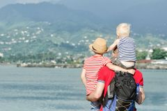 Father with two sons stand on the beach. View from the back Royalty Free Stock Photos