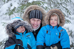 Father and two sons in  winter forest Royalty Free Stock Photos