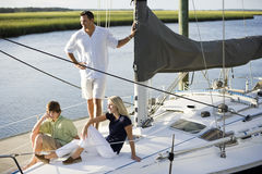 Father and two teenage children relaxing on boat Stock Photos