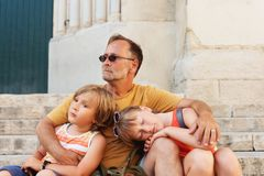 Father with two tired kids resting outside. Father with two tired kids resting on the church stairs. Long sightseeing day, travel with children Royalty Free Stock Images