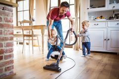 Father and two toddlers doing housework. stock photos