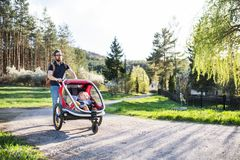 A father with two toddlers in jogging stroller on a walk outside in spring nature. A father with two toddler children sitting in jogging stroller on a walk Stock Photo