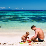 Father and two year old boy playing on beach Stock Photo