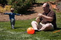 Father uses a bubble machine to produce bubbles that his young son runs after. Young boy runs after bubbles that the father produces with a bubble machine as he Royalty Free Stock Images