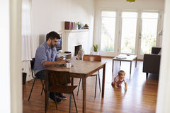 Father Uses Laptop Whilst Baby Son Plays On Floor Stock Image
