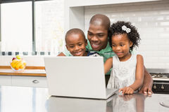 Father using laptop with his children in kitchen. In kitchen at home royalty free stock photo