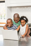 Father using laptop with his children in kitchen Royalty Free Stock Photos
