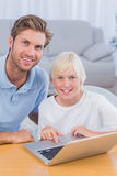 Father using laptop with his son. In the living room stock photo