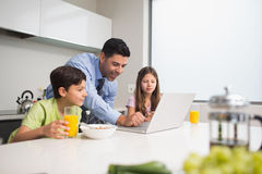Father using laptop and kids having breakfast in kitchen Stock Photos
