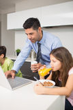 Father using laptop and kids having breakfast in kitchen Stock Images