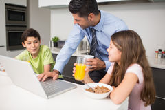 Father using laptop and kids having breakfast in kitchen Stock Photography