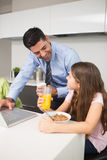 Father using laptop and kids having breakfast in kitchen Royalty Free Stock Photo