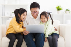 Father using laptop with little girls Stock Photography