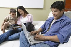 Father Using Laptop and mother and son Looking at DVDs on Couch Stock Photos