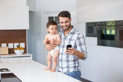 Father using mobile phone while holding baby boy Royalty Free Stock Photos