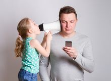Father using smartphone ignoring his daughter. Child tries to attract attention to himself, the parent ignores. in social networks royalty free stock image