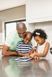 Father using tablet with his children in kitchen Stock Photo