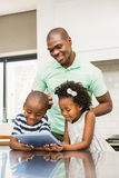 Father using tablet with his children in kitchen Royalty Free Stock Photography