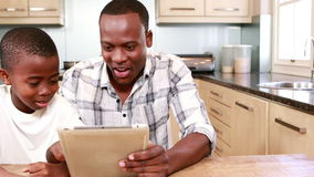 Father using tablet with his son stock footage