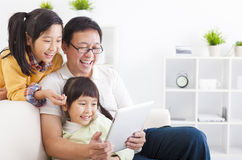 father using tablet pc with little girls
