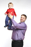 Father in violet shirt holds little boy. On the extended hands Stock Photos