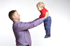 Father in violet shirt holds little boy. On the extended hands Stock Photography